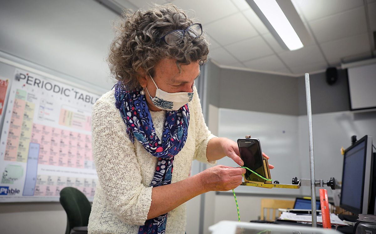 Science Instructor Alison Hobbie records a lab on her mobile phone.