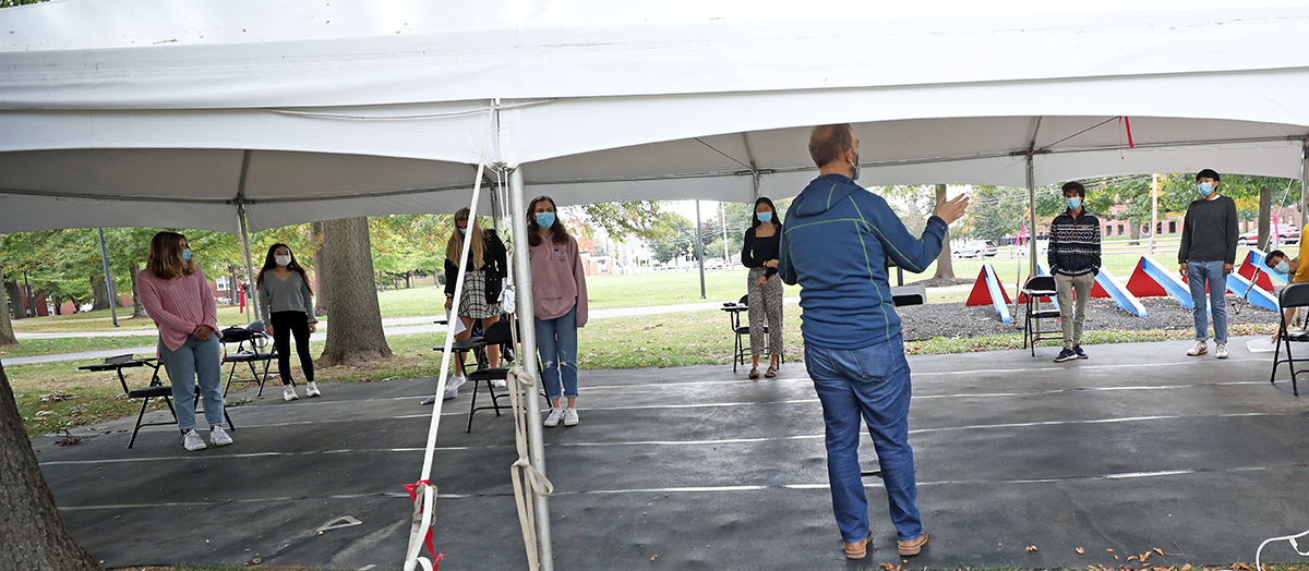 Music Department Chair Kris Johnson conducts rehearsal under a tent.