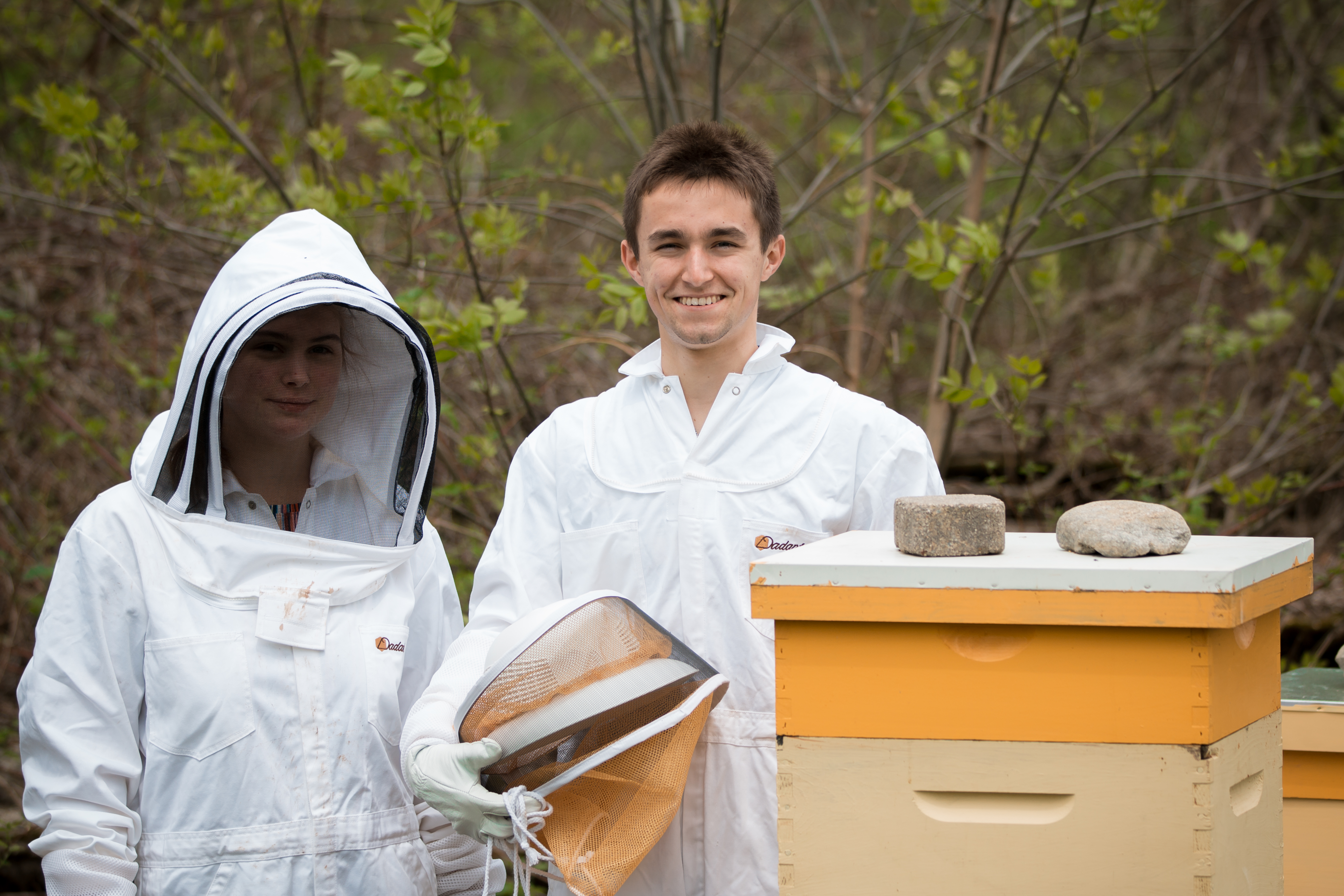 Hannah Johnson '19 and James Fortin' 18 stand beside Exeter's two beehives on South Campus.