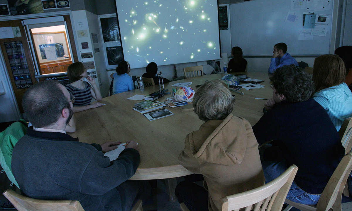 An astronomy class around the Harkness table with Instructor John Blackwell in the Phelps Science Center.