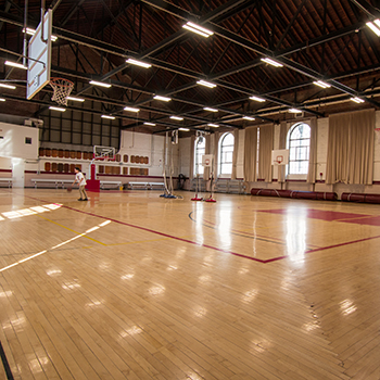 A student practices basketball inside of Thompson Gym