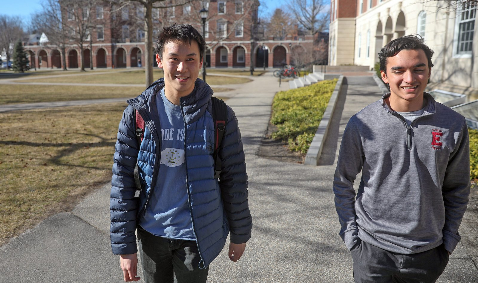 Ben Cai smiling as he walks the paths of Exeter's campus with a friend.