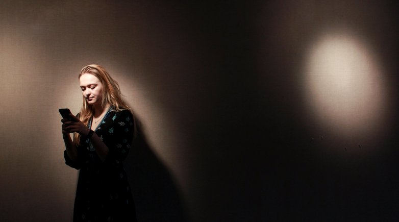 A girl stands in a spotlight while looking down at her cell phone.