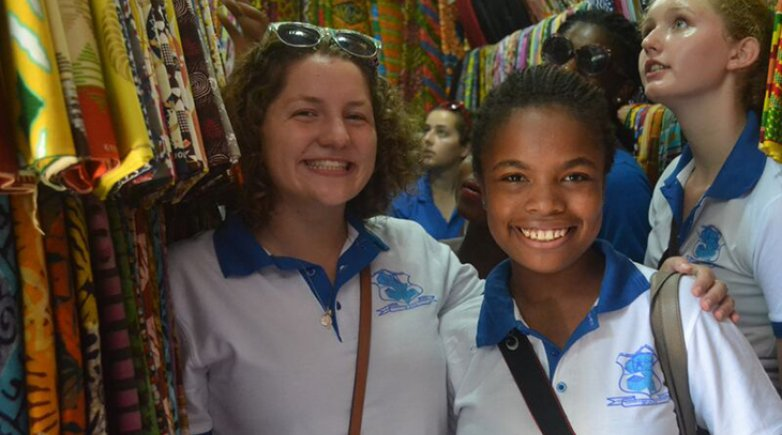 Exeter students smiling at a clothing market in Ghana
