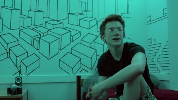 Ben Harrison sits in front of his decorated dorm room wall