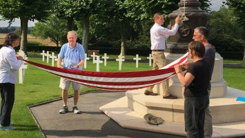 Exeter alumni help fold the American flag in the Aisne-Marne American Cemetery.