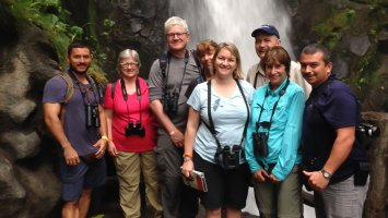 Exonians with birding expert and Biology Instructor Chris Matlack in front of a waterfall in Costa Rica.
