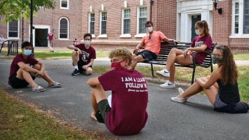 Exeter dorm proctors seated on the ground waiting to welcome students to campus.
