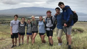 A group of Exeter students standing in front of the ocean in Maui