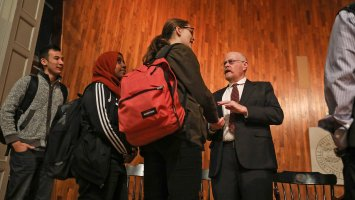Exeter alumnus Michael Shafer talks with students on Assembly Hall stage.