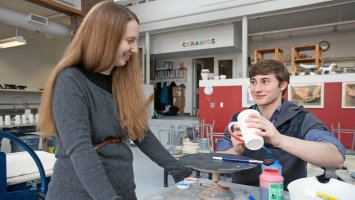 Carla Collins smiles as a student as he applies glaze to a ceramic mug