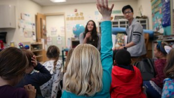 A second-grader at Main Street School raises her hand to ask a question during story time with Phillips Exeter Academy students.