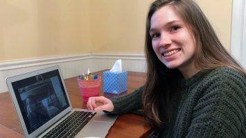Emma Cerrato sitting at a laptop computer