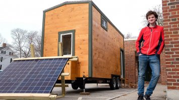Jed Breen '19 stands beside his senior project — a tiny house he built by hand.