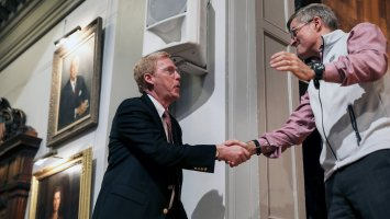 Bill Rawson shakes hands with Trustee Tony Downer in Exeter's Assembly Hall.
