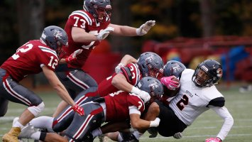 Exeter football players tackle an Andover player.