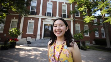 Exeter student Angela Zhang  in the front of the Academy Building