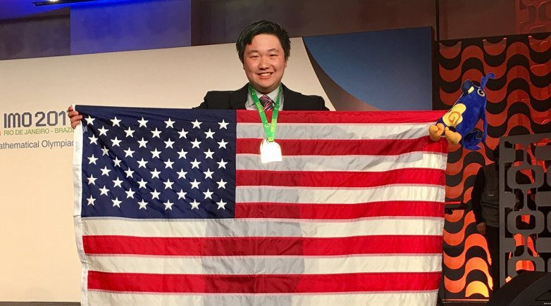 Exeter graduate James Lin a member of the winning team at the 59th International Mathematical Olympiad holding a US flag