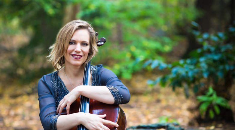 Velleda Miragias with a cello in the woods.