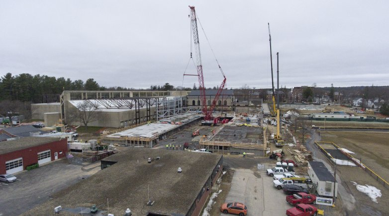 Cranes work to erect trusses on the new athletic field house at Exeter.
