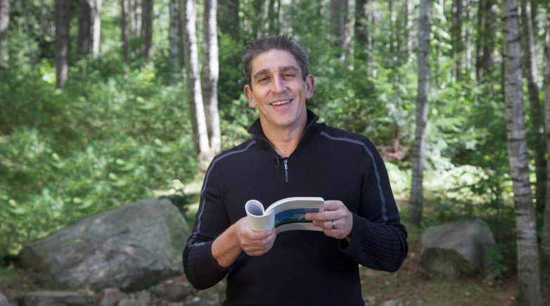 Writer Richard Blanco holding a book.