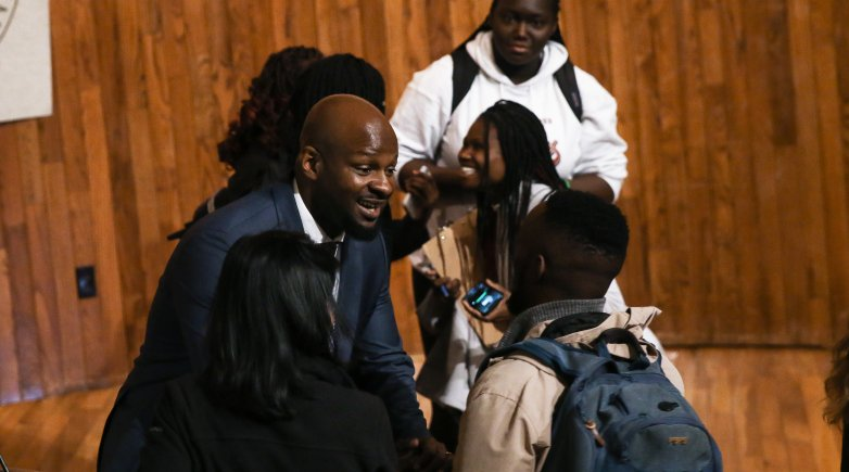 Alex Okosi '94 greets students after delivering his assembly remarks.