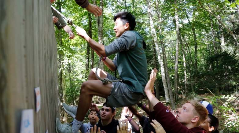 Members of the class of 2023 work together to overcome an obstacle during orientation activities at Brown Center