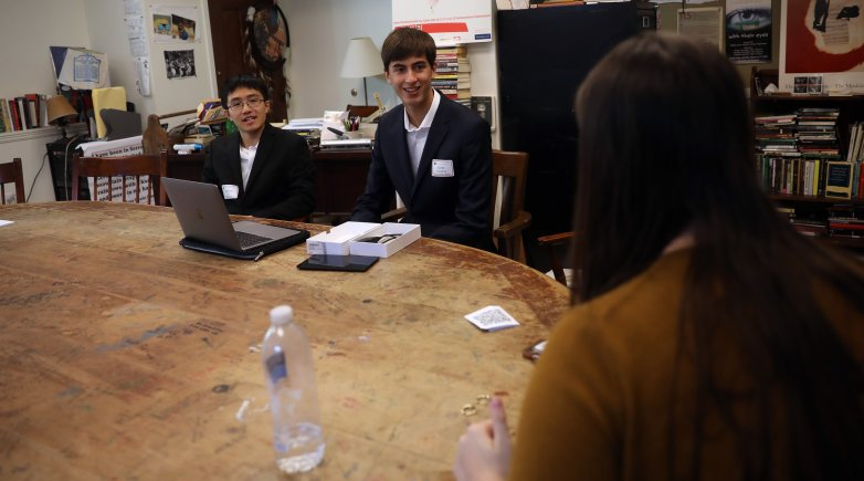 Harrison He '21 (left) and Evan Chandran '21 polish their pitch for a startup with mentor Emma Butler, a senior at Brown University, during the Emerging Entrepreneur Initiative.