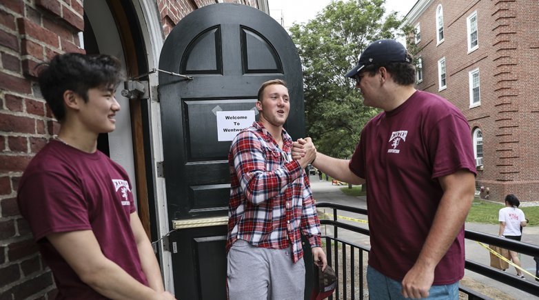 Exeter students greet each other outside of Wentworth Hall