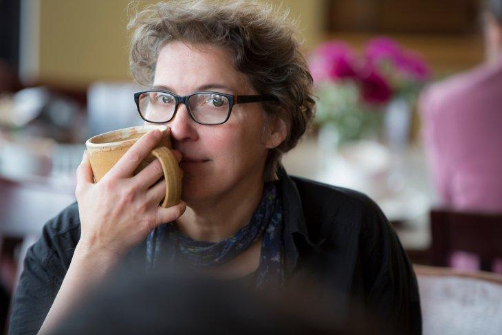 Shea holding a coffee mug close to her face.