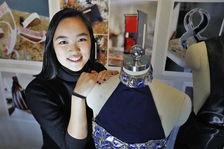 Ivy Tran with dresses she designed and made, one from candy wrappers.