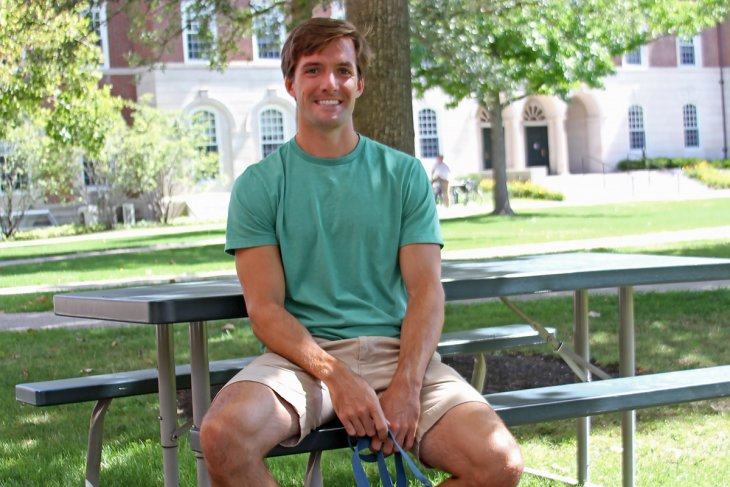 Tyler sitting at a picnic table on campus.