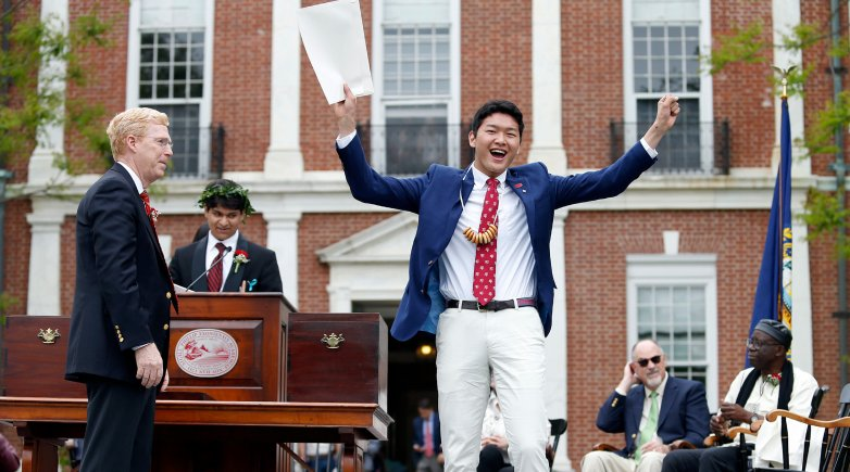 Student raises his diploma in the air with a look of joy at Exeter's Commencement.